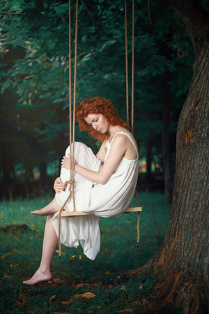 victorian girl: Beautiful thoughtful woman on a swing in the wood . Romantic and vintage portrait Stock Photo