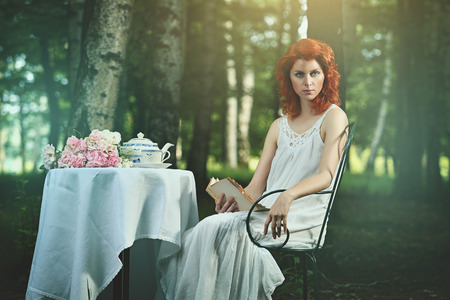 beautiful redhead: Surreal portrait of a beautiful redhead woman reading in the wood Stock Photo
