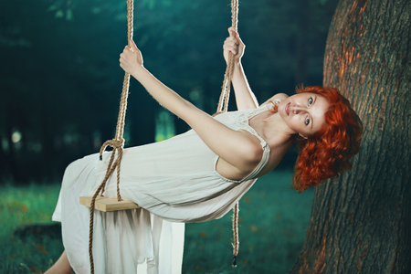 wood nymph: Beautiful woman with red hair on a swing in the forest