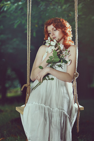 wood nymph: Romantic portrait of a beautiful woman with red hair. Swing in a forest Stock Photo
