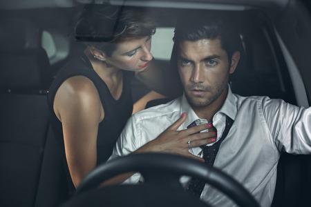 parejas sensuales: Mujer hermosa en el asiento trasero del coche seduce conductor. Moda y sensual Foto de archivo