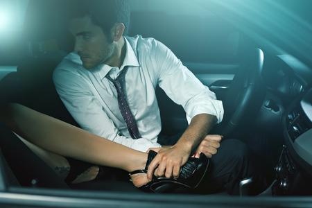 Handsome man in a car seduced by woman leg . Fashion and sensuality