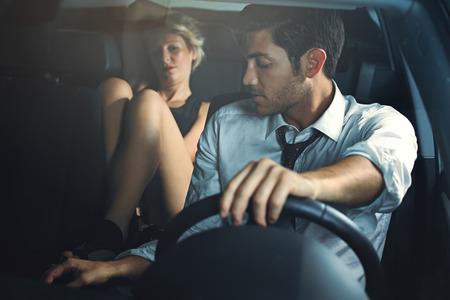 Knappe driver wordt verleid door sensuele vrouw op de auto achterbank Stockfoto