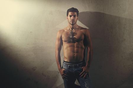 Uomo bello con corpo muscoloso in posa a torso nudo. Urban style e la moda