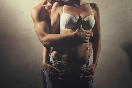 parejas romanticas: Torso detalle de pareja sin camisa contra la antigua muralla. Moda y sensual retrato