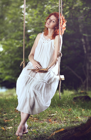 wood nymph: Beautiful red hair woman on a swing in the forest . Romantic portrait