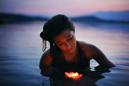 紫の湖沼における浮遊蝋燭を持つ美しい女性。美とロマンスの概念