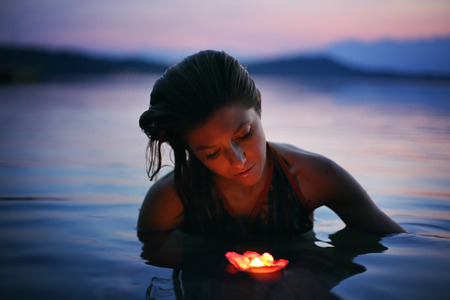 Beautiful woman with floating candle in purple lake waters . Beauty and romance concept Standard-Bild