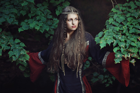 dark fantasy: Portrait of a medieval young lady among forest tree . Historical and fantasy Stock Photo
