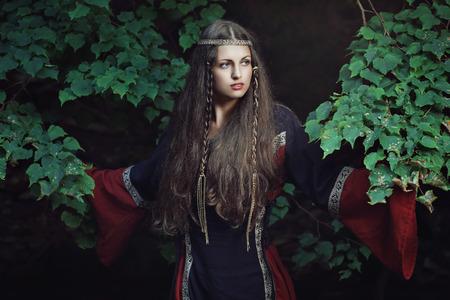 vestido medieval: Retrato de una joven dama medieval entre los árboles del bosque. Histórico y la fantasía Foto de archivo
