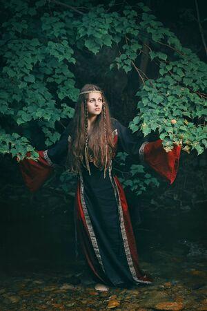 vestido medieval: Joven y bella mujer con vestido medieval en un arroyo del bosque