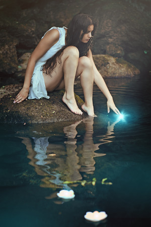 Beautiful wild nymph touching a water spirit. Fantasy and romantic concept