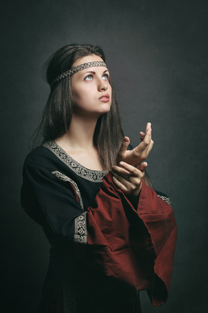 historical: Beautiful woman in medieval dress praying with eyes to the sky. Historical and religion