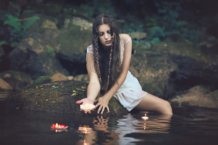 water nymph: Beautiful water nymph in forest stream with floating candles . Fantasy and romantic concept Stock Photo