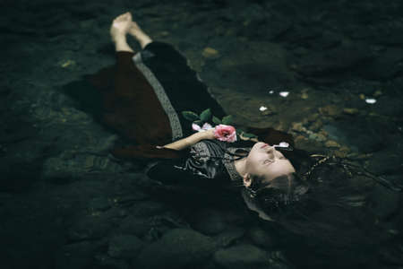 Beautiful floating dead woman in water . Ophelia conceptual Imagens