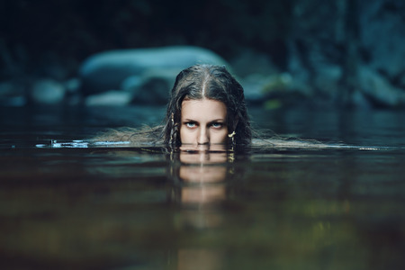 Dark water nymph with intense gaze . Ethereal and fantasy
