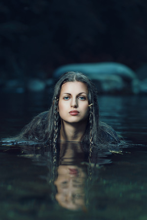 Beautiful water nymph in dark cyan stream . Ethereal and fantasy
