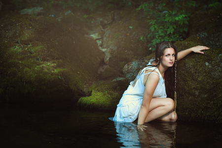 wood nymph: Beautiful woman posing in stream waters . Fantasy and surreal