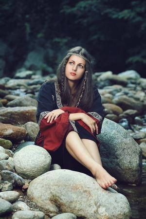 medieval: Mujer medieval hermosa sentado en las rocas de la corriente. Histórico y la fantasía