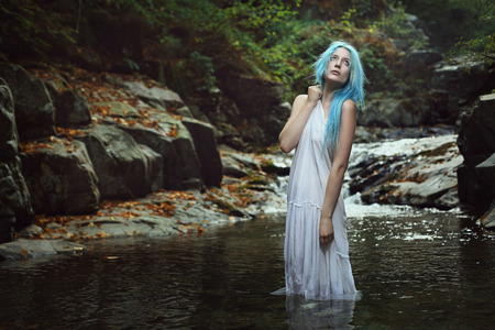 wood nymph: Beautiful ethereal maiden posing in mountain stream . Romantic and fantasy