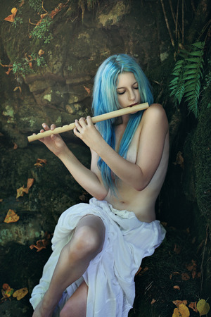 nymph: Forest maiden playing flute . Dreamy and fairy conceptual