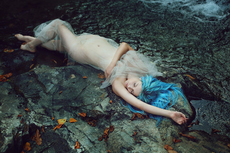 Beautiful river nymph sleeping on the stones . Fantasy and myth Stock Photo