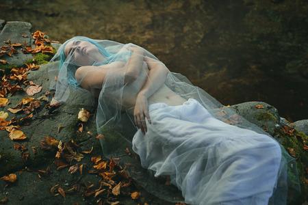 Sad bride posing on stream rocks . Decadence and loneliness concept