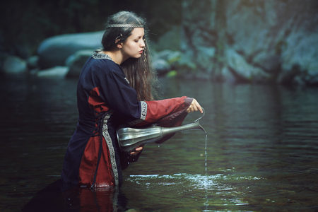 Ancient purification rite of a medieval woman in dark stream