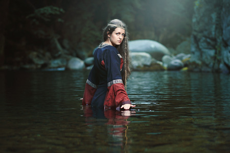 water nymph: Medieval woman in the middle of a dark stream. Fantasy and fairy Stock Photo