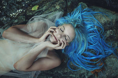 sea nymph: Beautiful mermaid sleeping on rocks . Fantasy and myth Stock Photo
