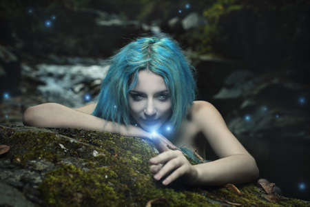 nymph: Curious dark dryad playing with forest magical spirits. Fantasy and halloween Stock Photo