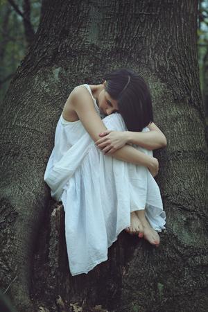 森の中の悲しい女性。孤独と憂鬱の概念