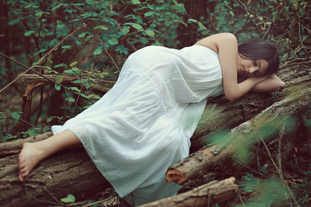 nymph: Sleeping woman on dead tree . Peace in nature Stock Photo