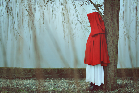 soledad: Mujer con capa roja en día brumoso y brumoso. Tristeza conceptual