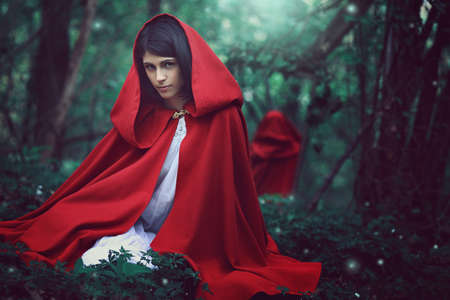 Dark little red riding hood in a surreal forest. Fantasy and fairy tale