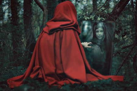 czarownica: Tajemnicza kobieta w czerwonym kapturze przed magicznym lustrze. Ciemny fantazja Zdjęcie Seryjne