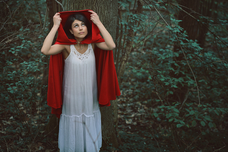 hood: Little red riding hood alone in dark forest before the storm . Fantasy and fairy tale Stock Photo