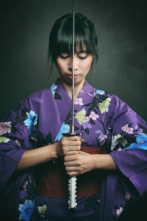 bookcover: Samurai woman ready to fight with katana . Studio dark shot