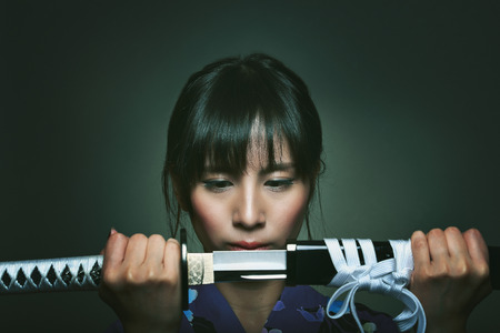 bookcover: Beautiful japanese woman with katana . Studio dark shot