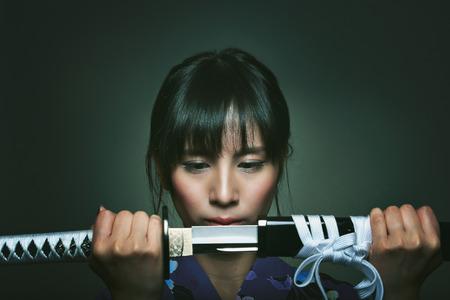 Mooie Japanse vrouw met katana. Studio donkere schot