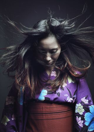 bookcover: Portrait of a japanese woman with traditional kimono . Studio dark shot