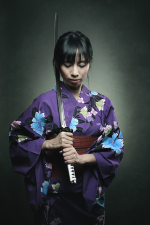 bookcover: Samurai woman with katana sword . Studio dark shot