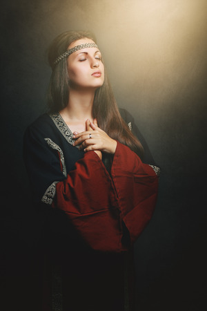 Beautiful medieval woman praying with eyes shut . Historical and religion
