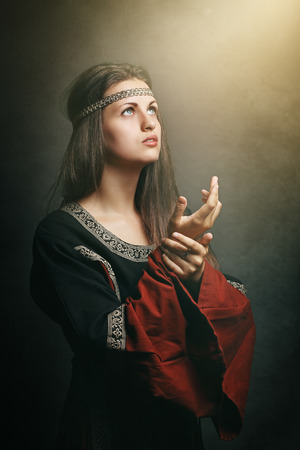 costumes: Medieval  woman with eyes to soft holy light. Historical and religion