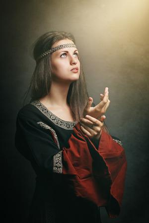 medieval dress: Mujer medieval con los ojos a la luz santa suave. Hist�rico y la religi�n