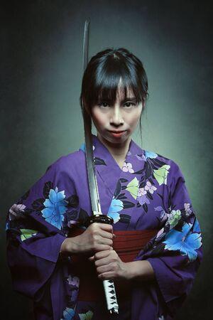 Portrait of a samurai woman . Studio dark shot Stock Photo