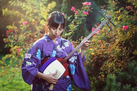 美しい日本女性の伝統的な楽器を演奏します。屋外のポートレート