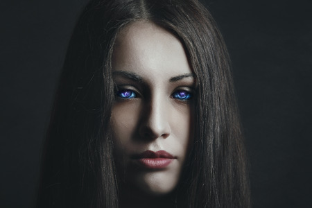 Dark portrait of beautiful girl with strange eyes. Surreal and alien Stock Photo