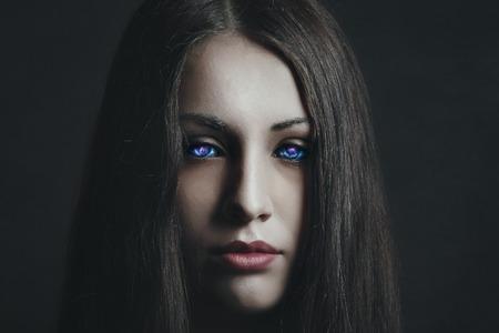 Dark portrait of beautiful girl with strange eyes. Surreal and alien Standard-Bild