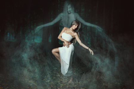 Beautiful dancer among ghosts of a misty forest . Surreal and Halloween Stock Photo